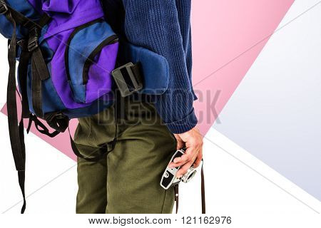 Midsection of backpacker hipster holding camera against rosa and white