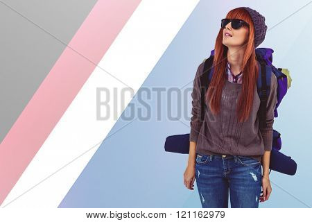 Portrait of a hipster woman with a travel bag against colored background