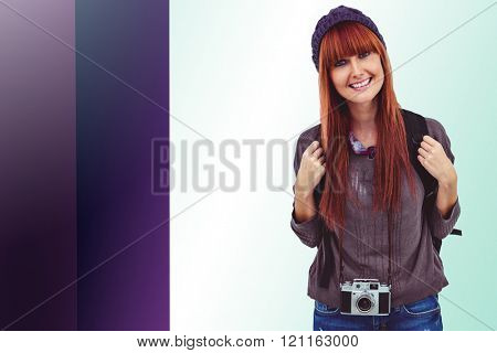 Portrait of a smiling hipster woman with a retro camera against colored background