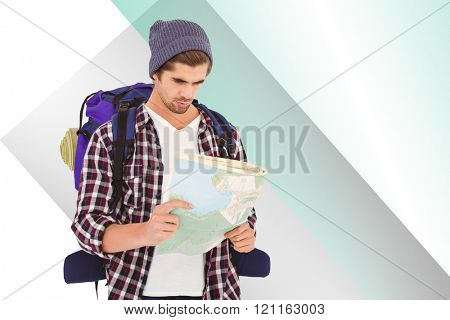 Man with luggage looking in map against colored background