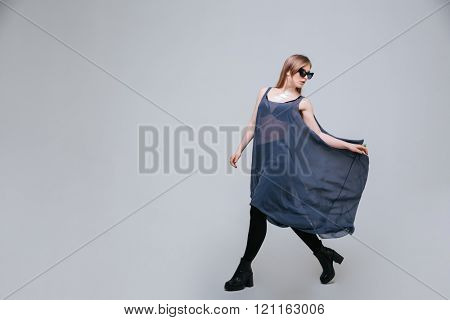 Full length portrait of a female model in fashion cloth posing over gray background