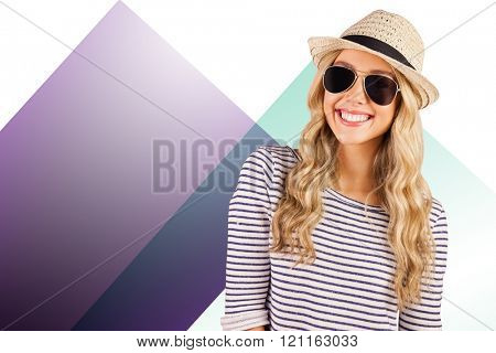 Gorgeous smiling blonde hipster with sunglasses and straw hat against colored background