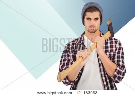 Portrait of confident man holding axe on shoulder against colored background