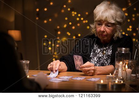 Elderly woman reading tarot cards