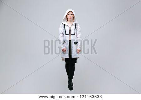Full length portrait of a female model standing over gray background