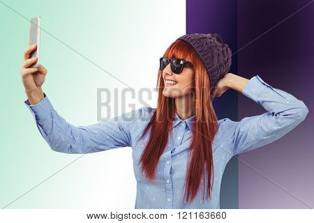 Smiling hipster woman taking selfie against colored background