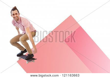 Businessman smiling while skateboarding against colored background