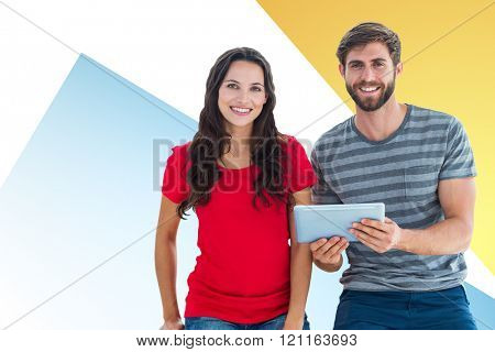 Couple posing with tablet against yellow and blue