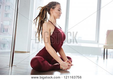 Focused pretty young woman with dreadlocks doing yoga in studio