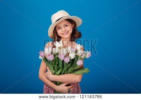 Portrait of cute happy little girl with bouquet of flowers over blue background