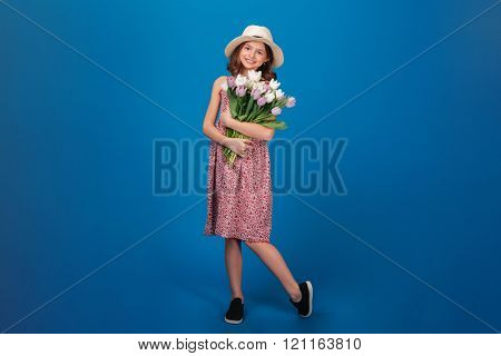 Full length of charming cheerful little girl standing and holding bouquet of flowers over blue background