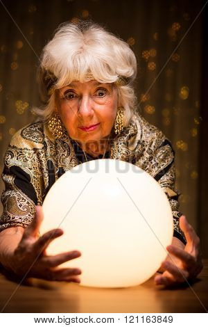Fortuneteller Looking Into Crystal Ball