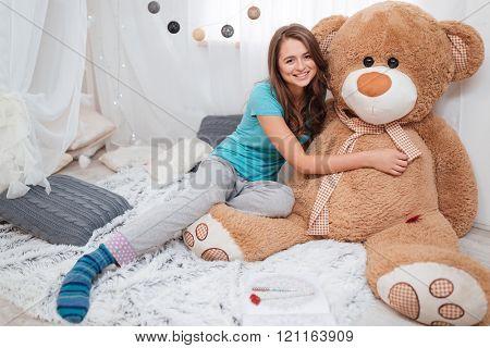 Pretty smiling girl sitting and hugging big plush bear at home