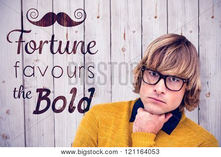 Portrait of thoughtful hipster businessman with hand on chin against wooden background
