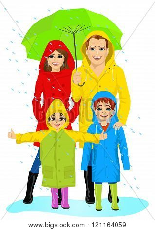 happy familt in raincoats standing with umbrella