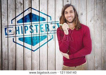 Portrait of happy hipster holding pen against wooden planks
