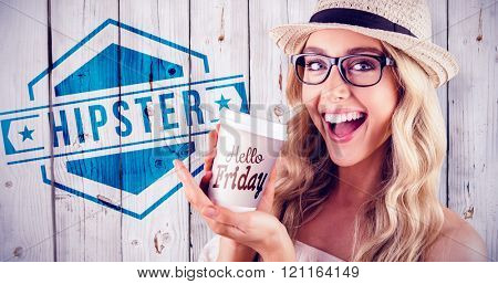 Gorgeous smiling blonde hipster presenting take-away cup against wooden background
