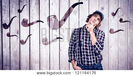 Focused hipster man thinking against wooden planks