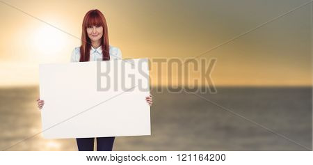 Attractive hipster woman holding white card against sunset of a beautiful day
