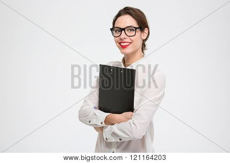 Happy beautiful young business woman standing and holding clipboard over white background