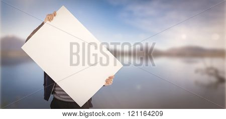 Man holding billboard in front of face against lake