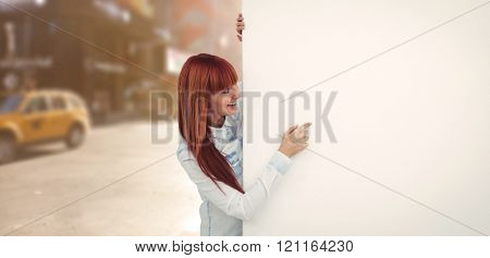 Smiling hipster woman behind a white card against blurry new york street