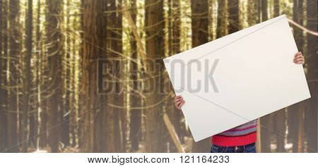 Hipster woman behind a big white card against trees in a woods