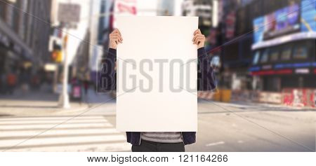 Man showing billboard in front of face against blurry new york street