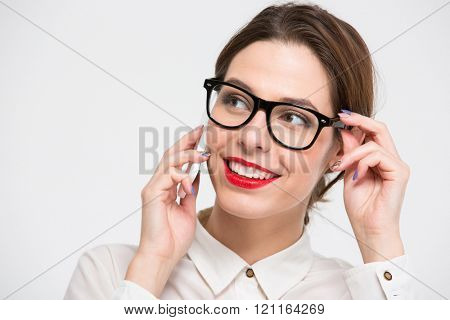 Closeup of cheerful pretty young business woman in glasses talking on cell phone over white background