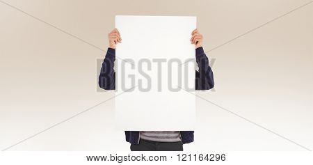 Man showing billboard in front of face against beige background