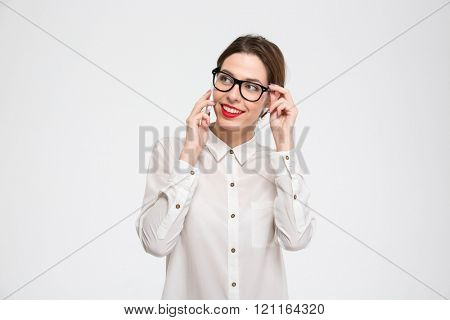Smiling beautiful young business woman in glasses standing and talking on smartphone over white background