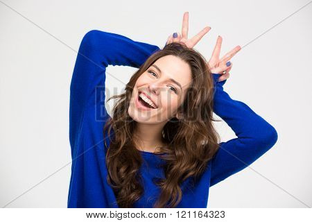 Smiling beautiful young woman having fun and making horns by her hands over white background