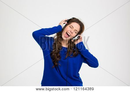 Happy pretty young woman in headphones listening to music and singing over white background