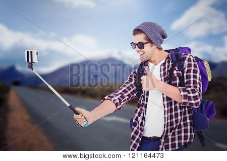 Happy man taking selfie against high angle view of road by mountains