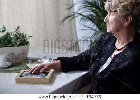 Woman holding husbund's photo