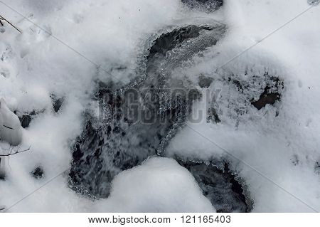 Frozen ice shape over fluent water in river