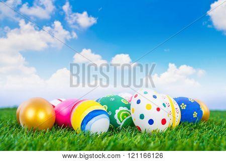 Easter Eggs on Fresh Green Grass over blue sky