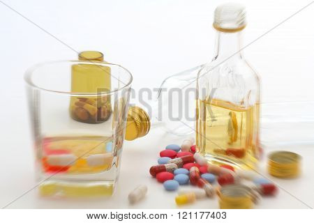 shot glass and liquor bottle with medications blurred on white background