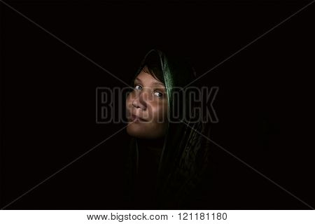 Beautiful Muslim young woman in darkness.  Dark room, the dim light of the flashlight