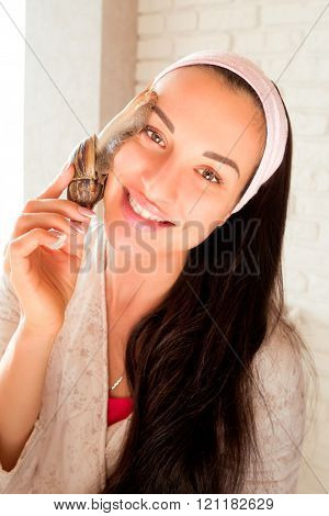 portrait of young smiling darkhaired woman with snails achatina giant on her face