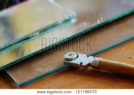 Old glass cutter and glass sheet on wooden background poster