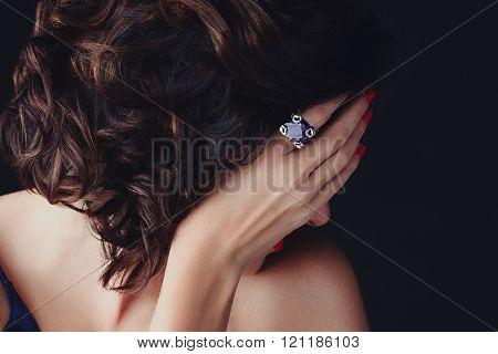 Woman, covering her face, a supphire ring