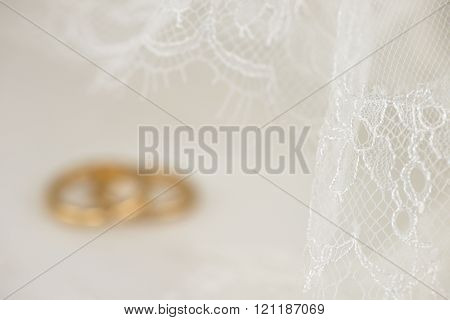 White wedding lace with golden rings in the background
