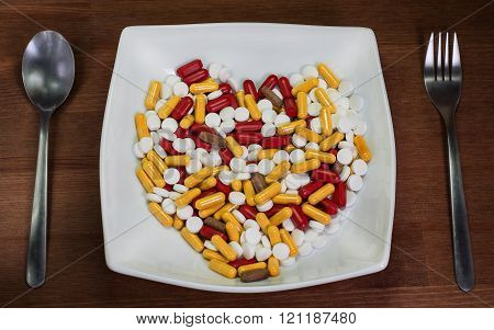 Be Healthy. Treatment With Pills. Many Pills In The Plate With Spoon. Heart.