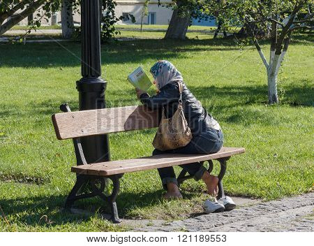 Kiev, Ukraine - September 11, 2015: Woman Parishioner Reading A Book In The Courtyard Of An Orthodox