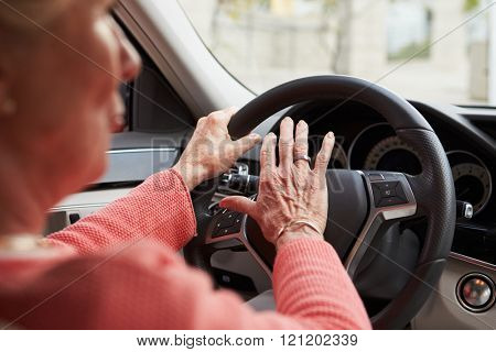 In car view of senior female driver using the horn in a car