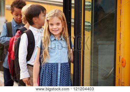 Elementary school girl at the front of the school bus queue