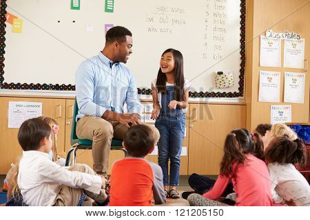 Schoolgirl at front of elementary class talking with teacher