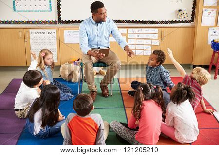 Elementary school kids sitting around teacher in a lesson