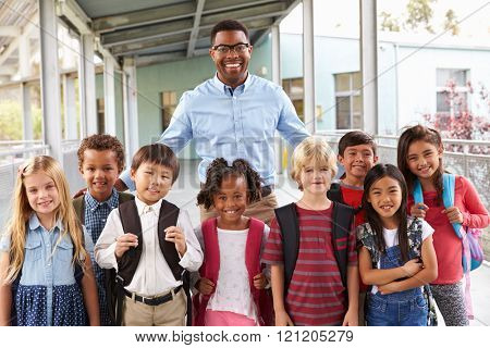 Portrait of elementary school kids and teacher in corridor